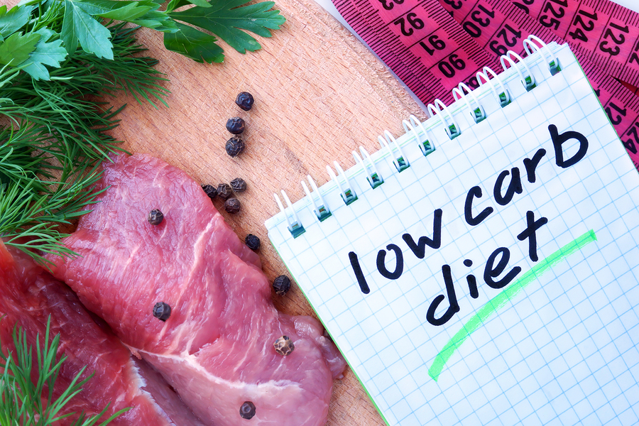 Notepad with low carb diet and fresh meat on wooden board