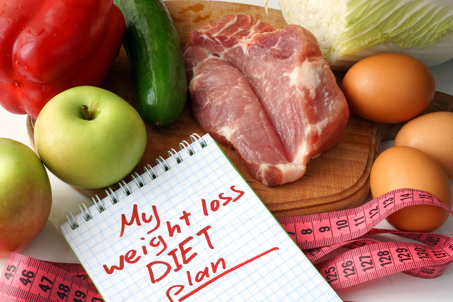 Notepad with weight loss diet plan and raw organic food.